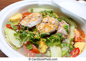 Sour soup in Vietnamese style with grouper fish in white...