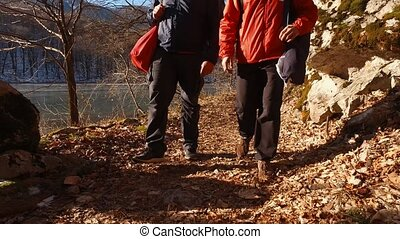 Legs of tourists walking through the woods. Snowy forest in the