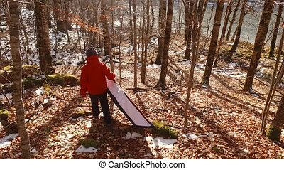 Tourist carries the kayak to the water in the forest. -...