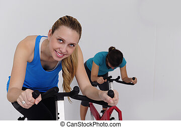 spinning; women czcling indoors at the gym - women doing...