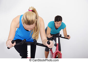 spinning; women cycling indoors at the gym - women doing...