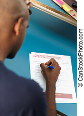 student filling application form - young adult...