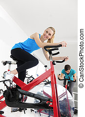 spinning; women cycling at the gym - spinning; happy women...