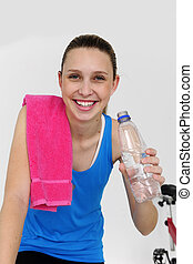 woman cycling at the gym and drinking water