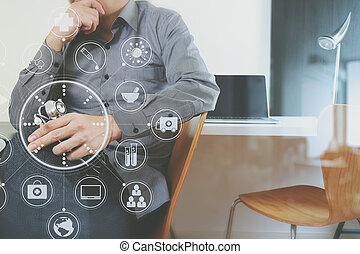 smart medical doctor holding stethoscope and thinking with laptop computer on dark wooden desk in modern office with virtual icon diagram