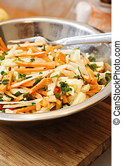 Kohlrabi and carrot salad with apple  ginger sauce on wooden board