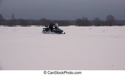 Snowmobile rides on winter field. 4K. - Snowmobile rides on...