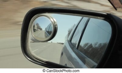 Back road reflected in car mirror, car driving fast on a...