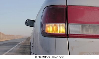 Flashing orange blinker light on rear lamp. car on a...