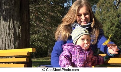 mother sit on bench with little baby daughter in autumn...