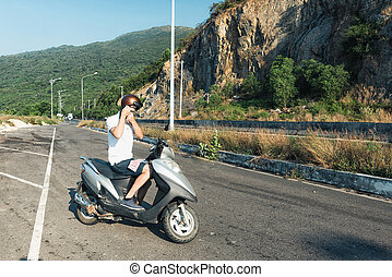 Biker putting on a helmet on parking - Young man in jeans...