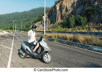 Biker in helmet and asian face mask - Young man in jeans...