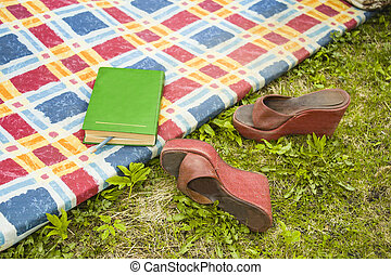 Reading In A Garden - A book on a mat and high heels on the...