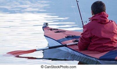 Fishing from a kayak on a lake. Red kayak