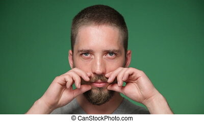 hipster man tightening up mustache and smiling - Close up...
