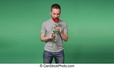 Young romantic man with a red rose