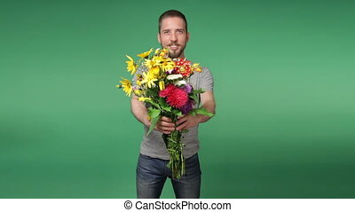 Young romantic man giving a bouquet of flowers