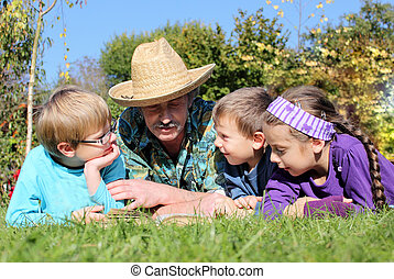 grandchildren with grandparents in the village, on the grass...
