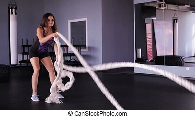 woman performing exercise with ropes - Functional training -...