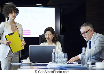 Three office workers in the board room