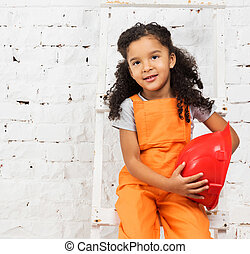 little girl in repairman uniform with helmet in hands