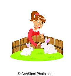 Smiling little girl petting two white rabbits in a mini zoo....