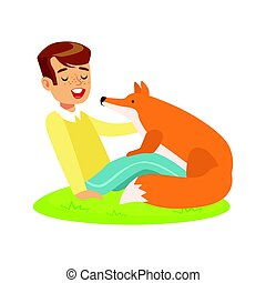 Smiling boy sitting on green grass and petting red fox....