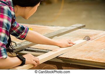 woman working on an electric buzz saw - woman carpenter...
