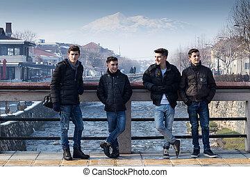four happy boys standing on the bridge of prizren, kosovo