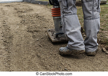Stamping soil with rammer to build the garden path