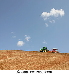 Farm Tractor Working in the Field with a Blue Sky