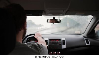 A back view of a man driving a car in the rain. Hands on a...