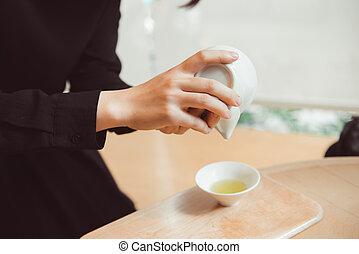 Hands holding Japanese Sencha Tea in clay pot.