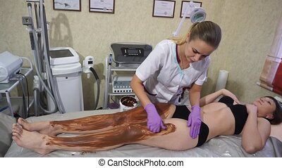 Woman during coffee chocolate massage procedure in a beauty...