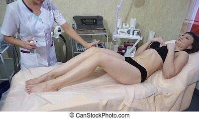 Beautician applying moisturizing cream on female legs in spa...