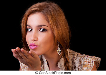 Pretty young caucasian girl sending kiss, with golden...