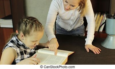 Mom helping her daughter do homework. schoolgirl makes...