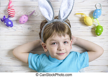 Easter concept. Happy cute child wearing bunny ears getting...