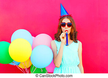 woman in a birthday cap with an air colorful balloons over a pink background