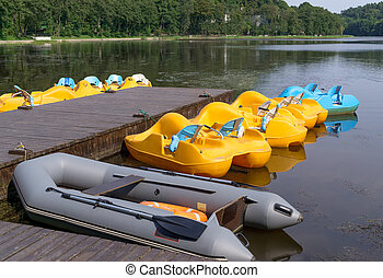 Parking pedalo on lake - Pedalos and inflatable boat parked...