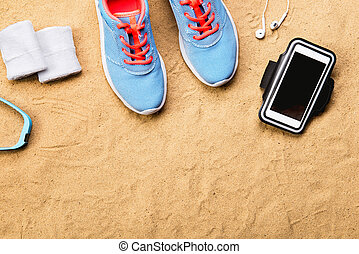 Sports shoes, earphones, smartphone against sand, studio...