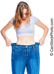 Portrait of a woman in old big jeans after losing weight on...