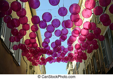 Pink balloons top of a provencal street, in France - Pink...