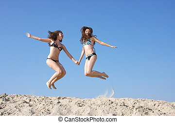 two beautiful girls on a sand-pit