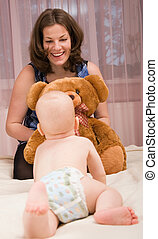Young mother playing with baby boy in bed