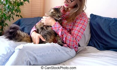 Beautiful woman stroking and hugging cat on the sofa. Home...