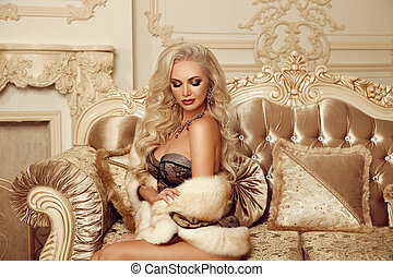 Beautiful alluring blond woman in fur coat sitting on royal sofa in luxury modern interior. Beauty glamour fashion style photo portrait.