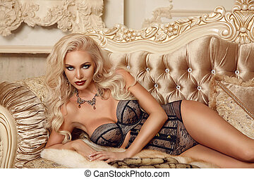 Beautiful alluring blond woman in sexy lingerie lying on...