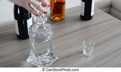 A female hand pours Russian vodka from a carafe into glass -...
