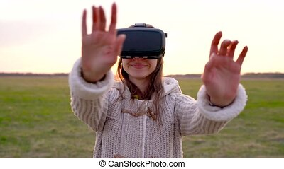 Girl uses a virtual reality glasses outdoors - Woman uses a...